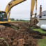 Excavator digging trenches for septic tank system replacement